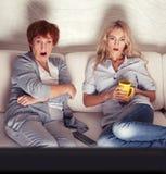 Moder med hållande ögonen på television för vuxen dotter Fotografering för Bildbyråer
