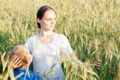 Moder med henne barn i fält arkivfoton