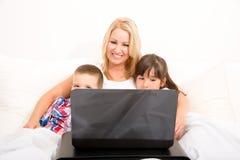 Moder med henne ungar som använder en bärbar dator i säng Arkivfoto