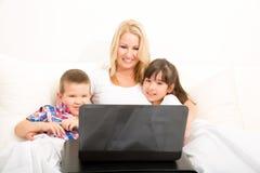 Moder med henne ungar som använder en bärbar dator i säng Arkivbilder