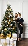 Moder med hennes barndotter som firar nära julgranen royaltyfri foto