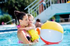 Moder med hennes dotter i simbassäng solig sommar royaltyfri fotografi