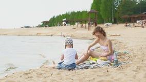 Moder med hennes dotter på en picknick vid floden på en solig dag stock video