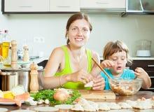 Moder med hennes dotter som gör morgonfiskklimparna i Arkivbild