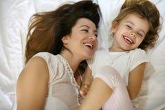 Moder med hennes gulliga lilla dottersammanträde på säng arkivfoton