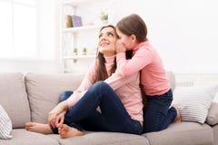 Moder med hennes gulliga lilla dottersammanträde på soffan arkivfoton