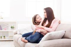 Moder med hennes gulliga lilla dottersammanträde på soffan fotografering för bildbyråer