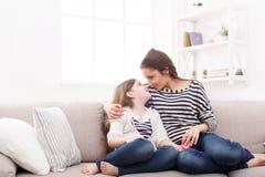 Moder med hennes gulliga lilla dottersammanträde på soffan arkivfoto
