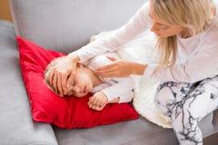 Moder med hennes hemmastadda sjuka unge Fotografering för Bildbyråer