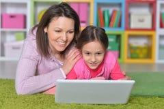 Moder med hennes lilla dotter som anv?nder b?rbara datorn arkivbild