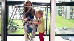 Moder med hennes litet barndotter som hänger den tvättade tvätterit på ställning i balkong