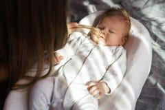 Moder med hennes nyfödda son på sängen i strålarna av solljus arkivbilder