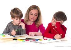 Moder med hennes söner som läser en bok Royaltyfria Foton