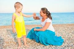 Moder med hennes son på ett Pebble Beach i aftonen Fotografering för Bildbyråer