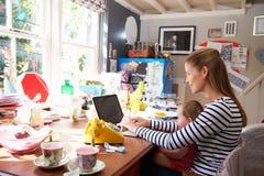 Moder med kontoret för små och medelstora företag för dotter det rinnande hemifrån Arkivfoton