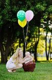 Moder med lilla flickan på bakgrund av gröna träd behandla som ett barn flaskflickan royaltyfri fotografi