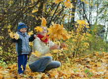 Moder med pojken som kastar lönnlöv Arkivfoto