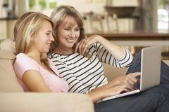 Moder med sammanträde för tonårs- dotter på Sofa At Home Using Laptop Royaltyfria Foton