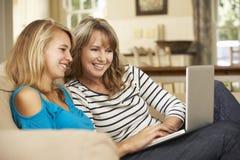 Moder med sammanträde för tonårs- dotter på Sofa At Home Using Laptop royaltyfri foto