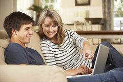 Moder med sammanträde för tonårs- son på Sofa At Home Using Laptop royaltyfri bild