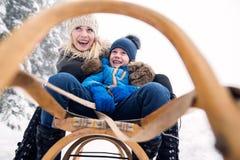 Moder med sonen på pulkan Dimmig vit vinternatur royaltyfria bilder