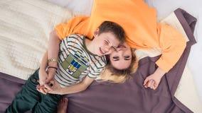 Moder med sonen på säng, moder och son som har gyckel arkivbild