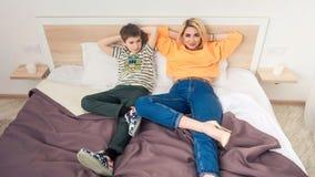 Moder med sonen på säng, moder och son som har gyckel fotografering för bildbyråer