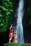 Moder med sonställningen under vattenfallet arkivfoton
