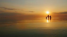 Moder med två barn som skrattar i havet på solnedgången lager videofilmer