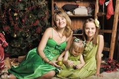 Moder med två döttrar i en grön klänning royaltyfri bild