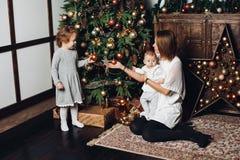 Moder med två ungar på julgranen royaltyfri bild
