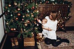 Moder med två ungar på julgranen royaltyfria foton