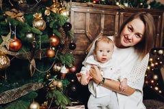 Moder med två ungar på julgranen royaltyfri fotografi