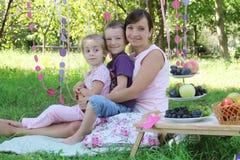 Moder med två barn som har sommarpicknicken Royaltyfri Foto