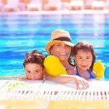 Moder med ungar i poolside arkivbild