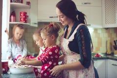 Moder med ungar på köket Arkivfoto