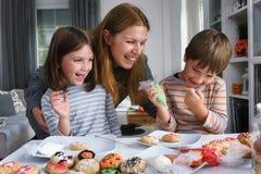 Moder med ungar som dekorerar kakor för allhelgonaafton royaltyfria foton