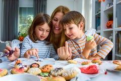 Moder med ungar som dekorerar kakor för allhelgonaafton fotografering för bildbyråer