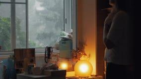 Moder med ungar som ut utanför ser fönstret, hällregn stock video
