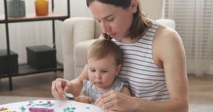 Moder och att behandla som ett barn dottern som spelar med plasticine arkivfilmer