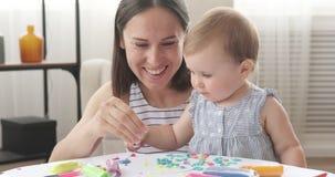 Moder och att behandla som ett barn flickan som hemma spelar med plasticine arkivfilmer