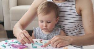 Moder och att behandla som ett barn flickan som spelar med plasticine stock video