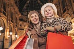 Moder och barn i julhatt med shoppingpåsar i Milan Arkivfoton