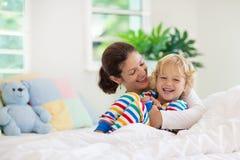 Moder och barn i säng Mamman och behandla som ett barn hemma arkivfoton