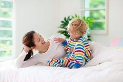 Moder och barn i säng Mamman och behandla som ett barn hemma royaltyfri bild