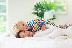 Moder och barn i säng Mamman och behandla som ett barn hemma royaltyfri fotografi