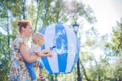 Moder och barn i tvålblåsare Är lycklig och glädje pojke som ler och skrattar Sommardagen parkerar in Fotografering för Bildbyråer