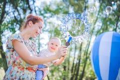 Moder och barn i tvålblåsare Är lycklig och glädje pojke som ler och skrattar Sommardagen parkerar in Royaltyfria Bilder