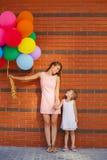 Moder och barn med färgrika ballonger Royaltyfri Foto