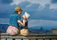 Moder och barn mot stadspanorama av Barcelona att kyssa Royaltyfri Bild